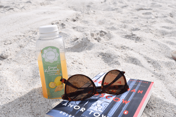 Juice, sunglasses and a book in the sand at St. Pete Beach