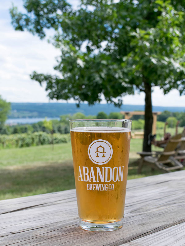 Full pint glass on picnic table with Keuka Lake in background